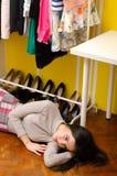 Ragazza alla moda sola triste che si trova sul pavimento sotto i suoi vestiti e scarpe Fotografia Stock