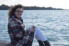 Ragazza alla moda sveglia di autunno che si siede dal lago Fotografia Stock Libera da Diritti