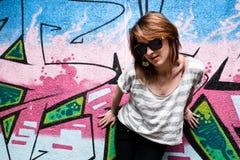 Ragazza alla moda in una posa di ballo contro la parete dei graffiti Fotografia Stock Libera da Diritti