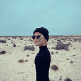 Ragazza alla moda in vestito nero su fondo del deserto Immagini Stock