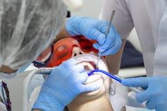 Ragazza alla ricezione al trattamento del dentista del dente cariato sopra la vostra carie dei denti fotografie stock