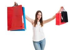 Ragazza allegra adorabile che sorride e che aumenta sui sacchetti della spesa colorati Fotografia Stock Libera da Diritti
