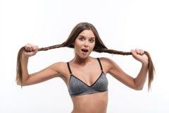Ragazza allegra che controlla forza di capelli Immagine Stock
