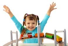 Ragazza allegra che gioca con la ferrovia del giocattolo fotografia stock