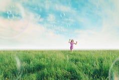 Ragazza allegra che gioca fra le bolle di sapone di estate fotografia stock libera da diritti