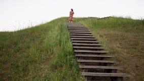 Ragazza allegra che guarda intorno sopra la collina del monticello con le scale di legno stock footage
