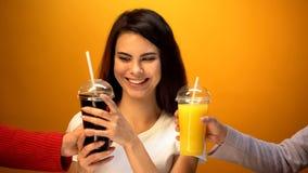 Ragazza allegra che sceglie soda invece del succo d'arancia, dipendenza alle bevande dolci fotografie stock