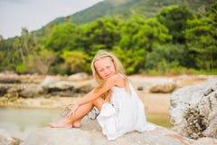 Ragazza allegra con capelli lunghi in un vestito bianco che si siede su una roccia dal mare immagini stock libere da diritti