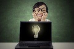Ragazza allegra con la lampadina sul computer portatile Immagini Stock Libere da Diritti