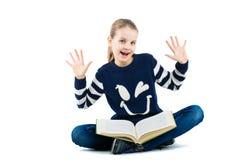 Ragazza allegra con le mani sollevate Ragazza che si siede sul pavimento con un grande libro Immagini Stock Libere da Diritti
