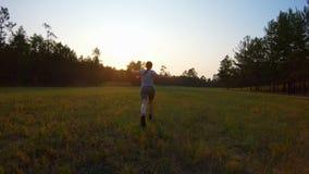 Ragazza allegra, correre steso di armi attraverso il campo al tramonto video d archivio