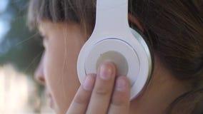 Ragazza allegra in cuffie che ascolta la musica e che balla nel parco di estate stock footage