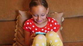 Ragazza allegra dell'adolescente che sorride e che utilizza smartphone sul sofà accogliente nell'aula magna video d archivio