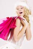 Ragazza allegra dell'assistente della Santa con i sacchetti di acquisto Fotografia Stock Libera da Diritti