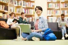 Ragazza allegra dello studente che utilizza computer portatile nella biblioteca immagini stock libere da diritti