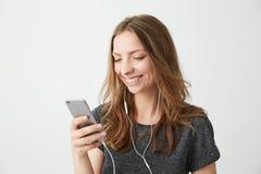Ragazza allegra felice che sorride esaminando lo schermo del telefono che ascolta il flusso continuo della musica sopra fondo bia immagini stock libere da diritti