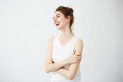Ragazza allegra felice con la risata sorridente del panino sopra il fondo bianco Armi attraversate Fotografia Stock