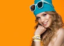Ragazza allegra intelligente nel cappello di sport, nel trucco variopinto, in riccioli e nel manicure rosa Fronte di bellezza immagini stock