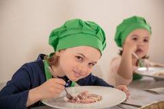 Ragazza allegra nel cibo del cappuccio del cuoco Fotografia Stock
