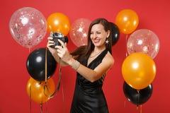 Ragazza allegra in poco vestito nero che fa prendendo selfie sparato sulla retro macchina fotografica d'annata della foto su fond fotografie stock libere da diritti