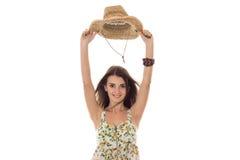Ragazza allegra in sarafan con il cappello floreale di paglia e di picchiettio con l'ampio bordo che sorride e che esamina la mac fotografie stock