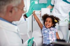 Ragazza allegra in sedia dentaria che fa scherzo con i dentis maschii immagini stock