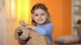 Ragazza allegra sorridente che guarda dall'orsacchiotto, divertendosi, infanzia felice fotografie stock