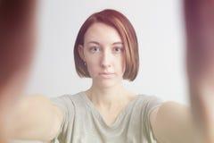 Ragazza allegra sorridente con le lentiggini che fanno selfie Allungamento del Th Fotografia Stock
