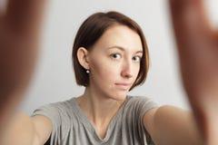 Ragazza allegra sorridente con le lentiggini che fanno selfie Allungamento del Th Immagine Stock