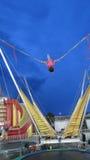 Ragazza alta su un trampolino del parco al crepuscolo Immagine Stock