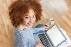Ragazza americana dello studente dell'africano nero che per mezzo di un computer portatile Immagini Stock