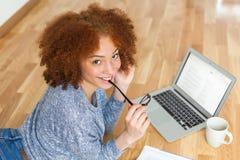 Ragazza americana dello studente dell'africano nero che per mezzo di un computer portatile Fotografia Stock