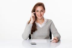 Ragazza amichevole di affari 20s che ascolta sul telefono allo scrittorio Fotografia Stock