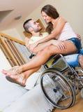 Ragazza amorosa con il suo ragazzo in sedia a rotelle fotografie stock libere da diritti