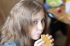 Ragazza 10 anni che mangiano i biscotti Sguardo espressivo luminoso, ritratto nel fondo molle della sfuocatura del fuoco fotografia stock libera da diritti