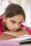 Ragazza annoiata che fa compito allo scrittorio in camera da letto Fotografia Stock