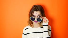 Ragazza annoiata con gli occhiali da sole in mani su fondo arancio vivo in studio Giovane adolescente arrogante video d archivio