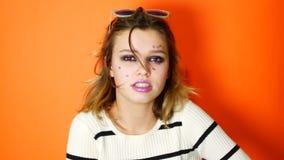 Ragazza annoiata con gli occhiali da sole in mani su fondo arancio vivo in studio Giovane adolescente arrogante archivi video