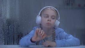 Ragazza annoiata in cuffie che ascolta la musica dietro la finestra piovosa, casa da solo video d archivio
