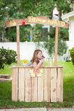 Ragazza annoiata senza i clienti al suo supporto di limonata Fotografia Stock Libera da Diritti