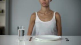 Ragazza anoressica che si siede davanti al piatto vuoto, acqua potabile, dieta severa fotografie stock