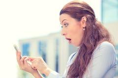 Ragazza ansiosa che esamina telefono che vede cattive notizie o le foto con emozione disgustosa Fotografie Stock