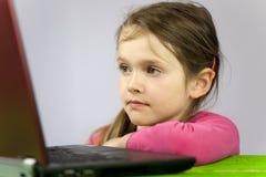 Ragazza anziana di sette anni con il computer portatile Immagini Stock Libere da Diritti