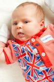 Ragazza appena nata che porta i vestiti britannici di simbolo Fotografie Stock