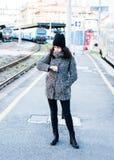 Ragazza arrabbiata che aspetta il suo treno per arrivare alla stazione ferroviaria Fotografia Stock