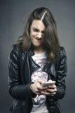 Ragazza arrabbiata che esamina telefono con emozione disgustosa Fotografia Stock
