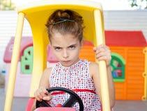Ragazza arrabbiata dei bambini del driver di automobile del giocattolo Immagine Stock