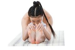 Ragazza asiatica in abiti sportivi che praticano in avanti piegare posa sulla stuoia di yoga Immagine Stock