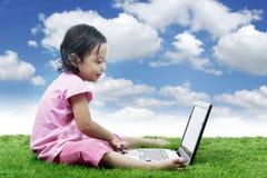 Ragazza asiatica allegra con il computer portatile Fotografia Stock