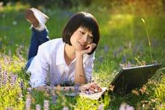 Ragazza asiatica attraente che per mezzo del computer portatile fra i fiori Fotografia Stock